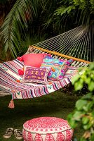 Pouffe below cushions with ethnic patterns in hammock in exotic garen