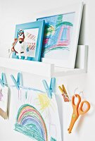 A child's drawings on a shelf and hanging on a washing line with pegs in a child's bedroom
