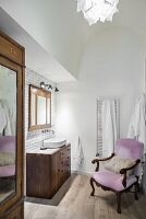 Old armchair with pink upholstery and dark wooden furnishings in bathroom