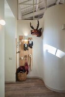 Curved wall in hallway and coat rack with stylised animal heads