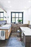 A bathroom with two washbasins, a window, a bath tub and large format, concrete-style tiles