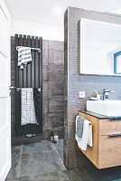 A partition wall in a bathroom with a radiator and large format, concrete-style tiles
