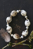 Circlet of threaded quail eggs and beads on black surface