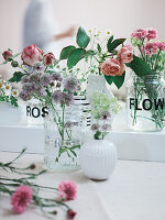 Homemade vases made from screw-top jars with stick-on flowers