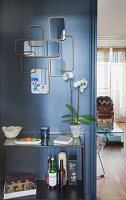 Arrangement of retro mirrors on grey wall above console table