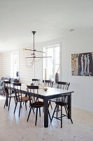 Black dining table and Windsor chairs on pale wooden floor