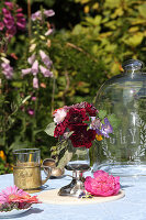 Posy in glass goblet on garden table