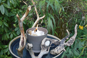 Candle lantern made from wax remnants decorated with twigs