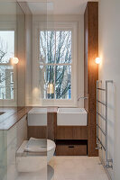 Small narrow bathroom with wooden fittings and toilet