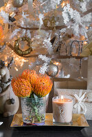 Vase of orange proteas and candle in jar on golden tray