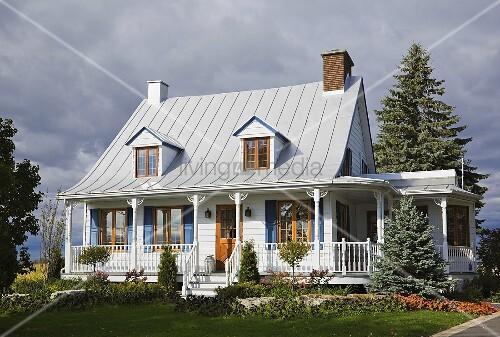Weisses holzverkleidetes giebelhaus mit kleinen for Modernes haus mit veranda