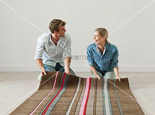 junges paar rollen teppich auf den boden bild kaufen living4media. Black Bedroom Furniture Sets. Home Design Ideas
