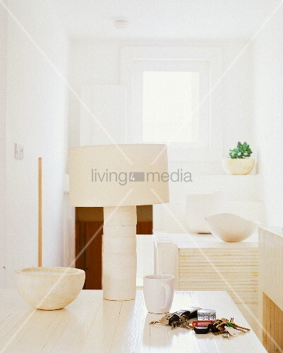 weisser holztisch mit cremefarbener tischlampe und kerzenschale teetasse und schl sselbund. Black Bedroom Furniture Sets. Home Design Ideas