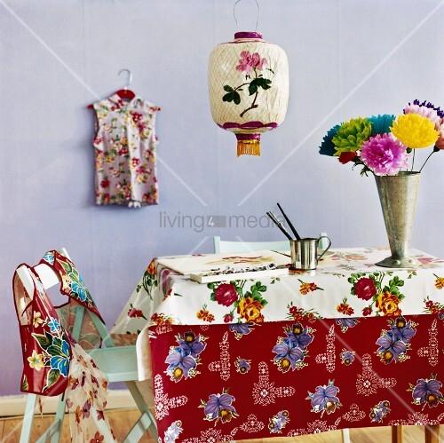 tisch mit farbenfroher tischdecke bunten blumen in der vase und malutensilien bild kaufen. Black Bedroom Furniture Sets. Home Design Ideas