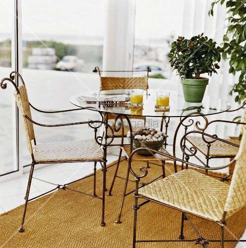 filigraner glastisch mit vier passenden flechtst hlen darauf orangensaft eine zeitung und eine. Black Bedroom Furniture Sets. Home Design Ideas