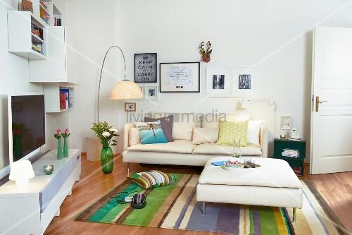 weisses medienm bel und h ngeregale zu cremefarbenem sofa mit ottomane gestreifter teppich. Black Bedroom Furniture Sets. Home Design Ideas