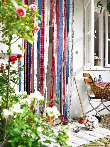 fliegenvorhang aus bunten stoffstreifen in der t r zum. Black Bedroom Furniture Sets. Home Design Ideas