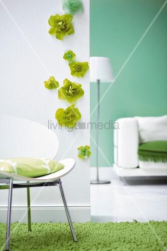 weisser stuhl mit kissen vor weisser wand mit gr nen papierbl ten daneben spiegel bild kaufen. Black Bedroom Furniture Sets. Home Design Ideas