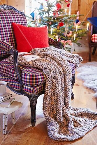 gestrickte decke mit kissen und buch auf sessel im. Black Bedroom Furniture Sets. Home Design Ideas