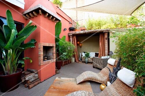 moderne rattanliegen und tropische pflanzen im k bel auf terrasse vor mediterranem wohnhaus mit. Black Bedroom Furniture Sets. Home Design Ideas