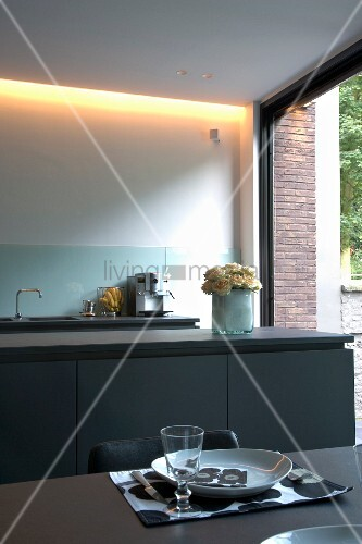 ein gedeck auf esstisch vor k chenzeile mit grauen unterschr nken und indirekte beleuchtung vor. Black Bedroom Furniture Sets. Home Design Ideas
