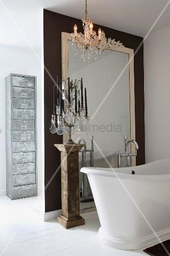 freistehende vintage badewanne und mehrarmiger kerzenst nder auf antiker stele vor raumhohem. Black Bedroom Furniture Sets. Home Design Ideas