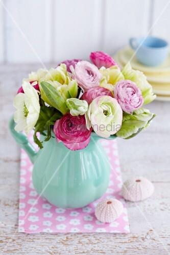 strau aus ranunkeln wei en anemonen und wei en tulpen in einem krug neben seeigelgeh usen. Black Bedroom Furniture Sets. Home Design Ideas