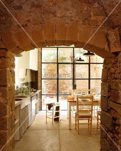 blick durch naturstein durchbruch ins esszimmer mit k che auf tisch vor terrassent r bild. Black Bedroom Furniture Sets. Home Design Ideas