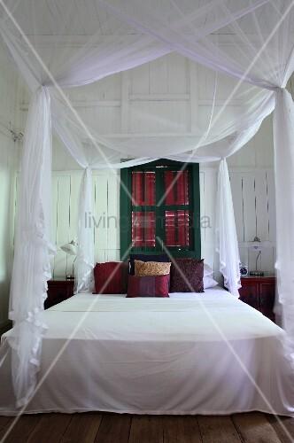 himmelbett mit luftigem weissem stoff vor gr n gestrichenem fenster mit geschlossenen l den. Black Bedroom Furniture Sets. Home Design Ideas