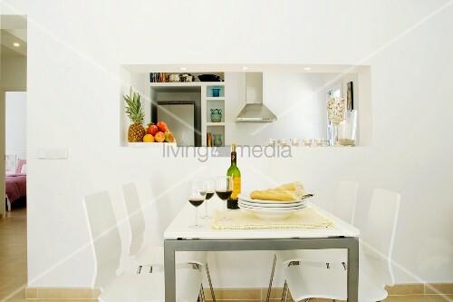 moderner essplatz in weiss mit rotwein und brot gedeckt vor k chendurchreiche bild kaufen. Black Bedroom Furniture Sets. Home Design Ideas