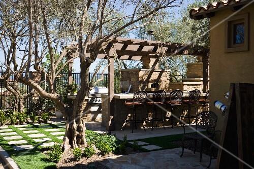 sonniger terrassenplatz im garten mit gemauerter bar unter pergola und rustikalem kamin bild. Black Bedroom Furniture Sets. Home Design Ideas