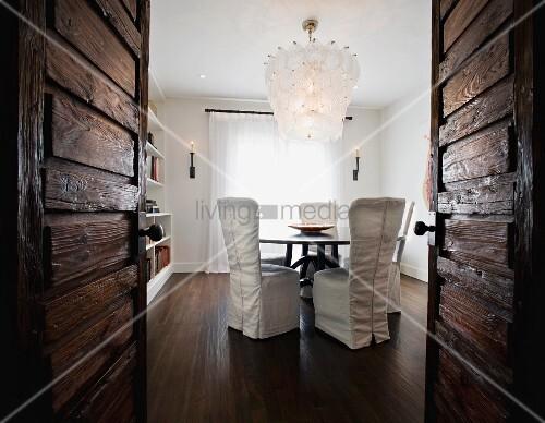 blick durch offene rustikale t ren auf essplatz mit hussen st hlen und elegantem leuchter. Black Bedroom Furniture Sets. Home Design Ideas