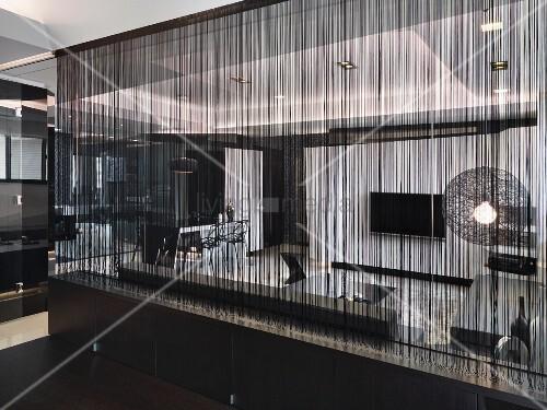 dunkler fadenvorhang vor glastrennwand und blick in wohnraum bild kaufen living4media. Black Bedroom Furniture Sets. Home Design Ideas