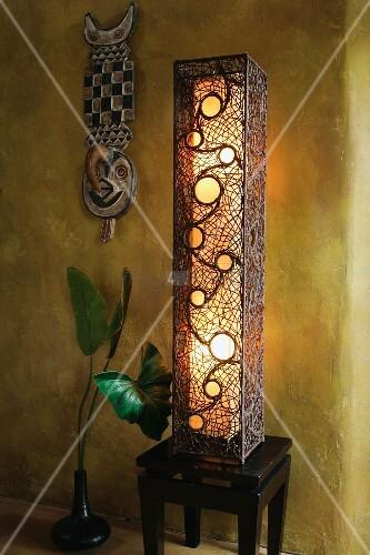 stehlampe auf hocker aus dunklem holz und afrikanische. Black Bedroom Furniture Sets. Home Design Ideas