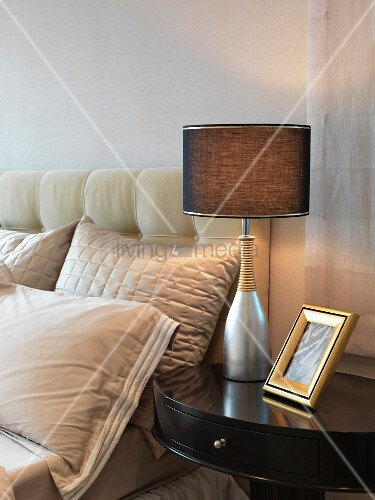 traditionelles nachttischchen mit tischlampe neben bett und gepolstertem kopfteil bild kaufen. Black Bedroom Furniture Sets. Home Design Ideas