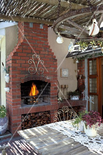 view across wooden table of fire in brick outdoor fireplace on veranda bild kaufen living4media. Black Bedroom Furniture Sets. Home Design Ideas
