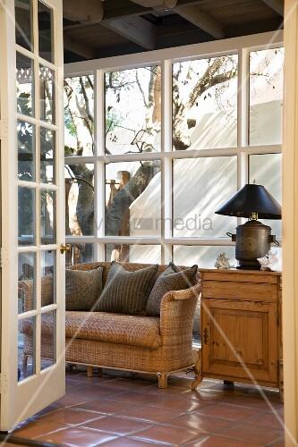 korbsofa und holzschr nkchen mit lampe in einem wintergarten bild kaufen living4media. Black Bedroom Furniture Sets. Home Design Ideas