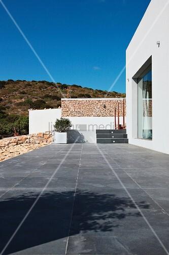 terrasse mit grauen fliesen vor zeitgen ssischem wohnhaus in mediterraner lage bild kaufen. Black Bedroom Furniture Sets. Home Design Ideas