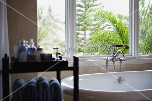 freistehende badewanne mit standarmatur vor dem fenster und kosmetikregal verschwommen im. Black Bedroom Furniture Sets. Home Design Ideas