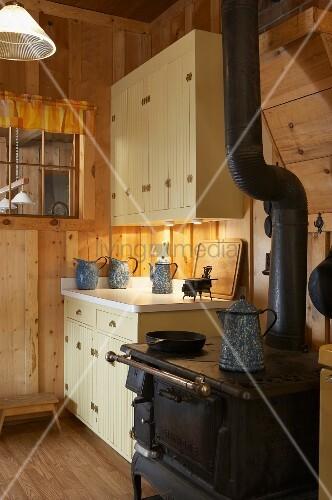 alter kaminofen in k che einer rustikalen holzh tte bild. Black Bedroom Furniture Sets. Home Design Ideas