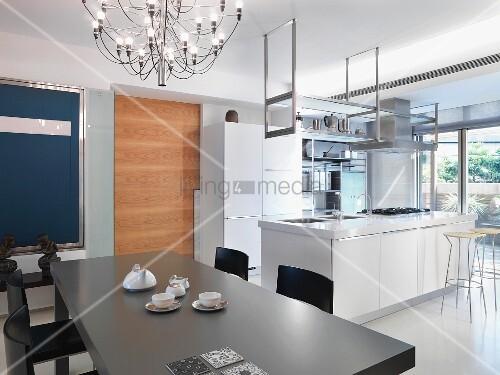 grauer esstisch unter designer h ngelampe vor offener k che mit freistehendem k chenblock in. Black Bedroom Furniture Sets. Home Design Ideas