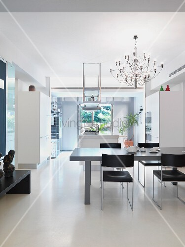 grauer esstisch und schwarze st hle unter designer h ngelampe in offenem minimalistischen. Black Bedroom Furniture Sets. Home Design Ideas