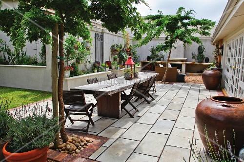 rustikaler tisch und st hle aus dunklem holz auf terrasse mit steinboden bild kaufen. Black Bedroom Furniture Sets. Home Design Ideas