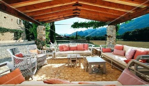 berdachte terrasse mit sofagarnitur und korbst hlen auf natursteinboden bild kaufen. Black Bedroom Furniture Sets. Home Design Ideas