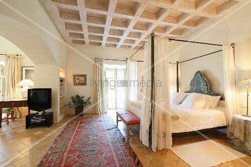 himmelbett mit vorhang unter kassettendecke aus holz in mediterranem schlafzimmer bild kaufen. Black Bedroom Furniture Sets. Home Design Ideas