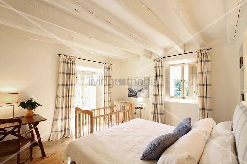 Schlichtes Schlafzimmer mit Kinderbett und weiss getünchte ...