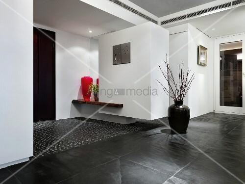 bodenvase mit zweigen auf dunkelgrauen schieferboden im. Black Bedroom Furniture Sets. Home Design Ideas