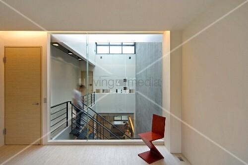 Küchenzeile Glaswand ~ klassikerstuhl aus rot lackiertem holz vor glaswand und