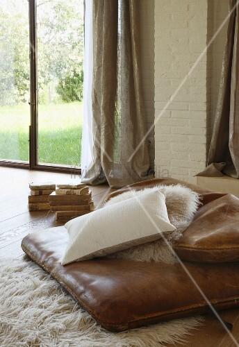 lederpolster kissen und flokatil ufer auf dielenboden vor terrasssenfenster bild kaufen. Black Bedroom Furniture Sets. Home Design Ideas
