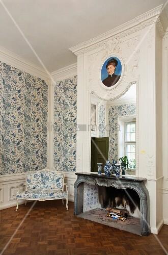 spiegel und portrait ber dem kamin in einem eleganten raum mit blau weiss gemusterter tapete. Black Bedroom Furniture Sets. Home Design Ideas
